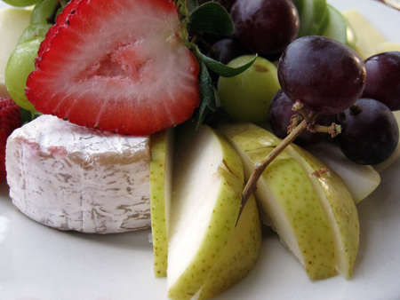 Close-up of Fruit and Cheese on a white plate.  Featuring Strawberries, grapes, pears slices