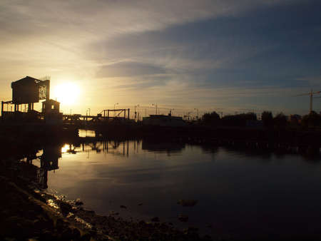 Sunrises over Mission Creek and the 4th street bridge with construction cranes in the distance. Stock Photo - 9671111