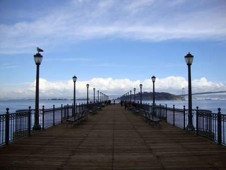 Long wooden pier in San Francisco with Bay Bridge and Treasure Island in the distance