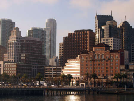 San Francisco Pier and Cityscape as rising sun reflects on buildings on a nice day  photo