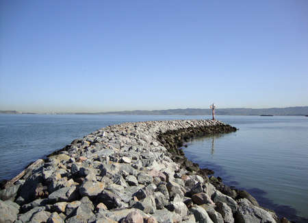 Curved Rock Jetty with light beacon at end in San Francisco Bay.