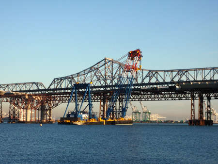 Large Crane on Barge lifts section of bay bridge into place in San Francisco Bay, California