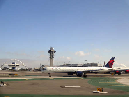 LA - JULY 26: Delta Plane sits on Runway at LAX with watchtower and iconic restaurant in the background. Taken July 26, 2012, LA , CA.