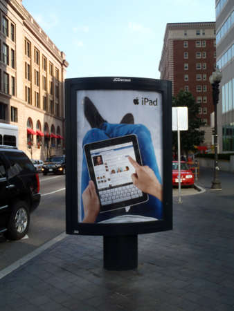 ipad2: BOSTON - JUNE 1: IPad Ad featuring Facebook use on an outdoor Ad stand on sidewalk of busy street. June 1, 2010 in Boston MA.