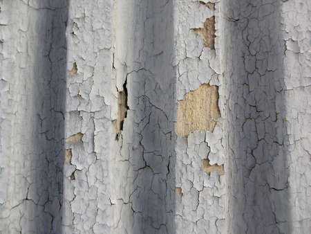 grooved: Crack gray paint on grooved wall showing the surface underneath