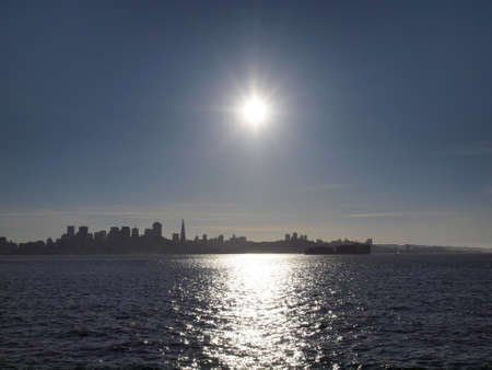Sunset Over San Francisco Cityscape and Bay with cargo ship passing in the foreground   photo