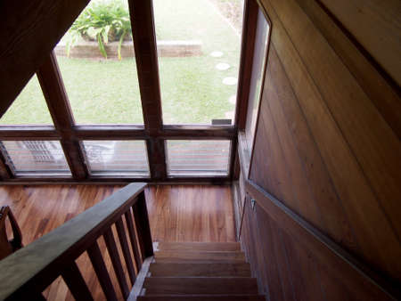 Wood Staircase leading downstairs to the dinning room with large windows featuring views of outside photo
