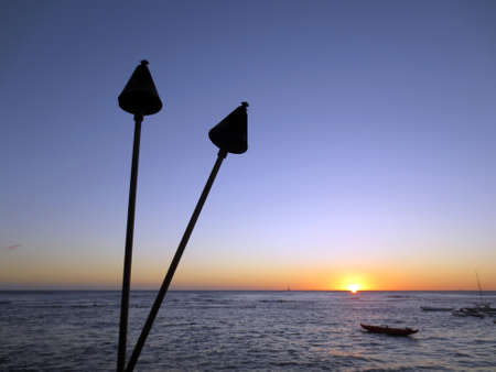 Sunset on Pacific Ocean with tiki torches, canoes, and boats off the shore of Waikiki on Oahu  Stock Photo - 18153297