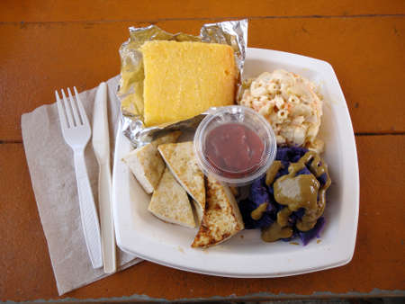 Tofu Slices, Sweet Potato, corn bread, and mac salad on a square plate and plastic fork and knife on a picnic table Stock Photo - 18153535