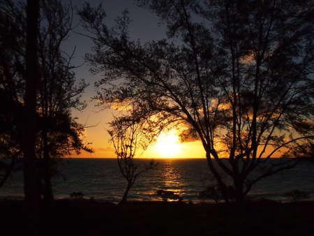 Sunrise burst over the ocean on Waimanalo Beach on Oahu, Hawaii with tree silhouettes Stock Photo - 18153952