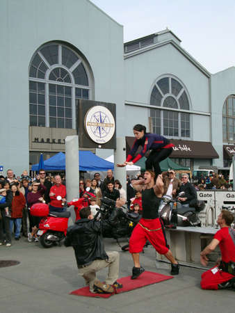 he   my sister: SAN FRANCISCO- JANUARY 16: performers almost drops his sister which he is balancing on his shoulders as he was trying to pass her to a man squatting from crowd January 16, 2010 at Ferry Building San Francisco.