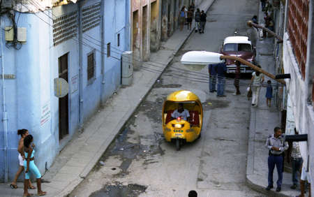 HAVANA, CUBA - JULY 25: Coco Taxi moves down small street filled with people in Havana and police officer taken July 25, 2004 Havana, Cuba. Stock Photo - 18306236