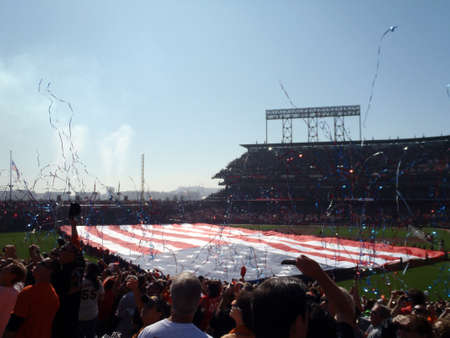 SAN FRANCISCO, CA - OCTOBER 19: San Francisco Giants vs. Philadelphia Phillies: Streamers fly in the air as people cheer with Large USA Flag held across the outfield by a line of people during national anthem before the start of game three of the NLCS 201 Stock Photo - 18306239
