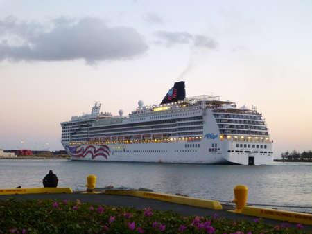 HONOLULU, HI - MAY 19: NCL Cruiseship, Pride of America,  leaves Honolulu Harbor at Dusk full of passangers  taken May 19, 2012 Honolulu, Hawaii. Stock Photo - 18306240