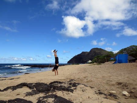 Man wearing a hat, t-shirt, shorts, and slippers Handstanding at Makapuu Beach with tents and lighthouse on cliff in the distance on Oahu, Hawaii. photo