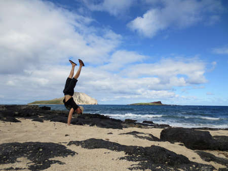 Man wearing a hat, t-shirt, shorts, and slippers Handstanding at Makapuu Beach with Rabbit (Manana) and Rock ( Kaohikaipu) islands in the ocean on the horizon line on Oahu, Hawaii. photo