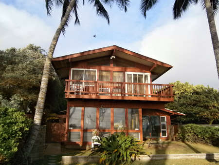Two Story Red Beach House with tall coconut trees on Oahu, Hawaii with bird flying overhead. Stock Photo