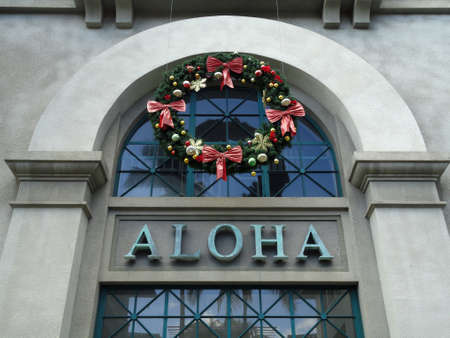 The Word Aloha and Christmas Wreath on side of Aloha Tower building. Aloha Tower is a lighthouse that is considered one of the landmarks of the state of Hawaii in the United States. Opened on September 11, 1926.