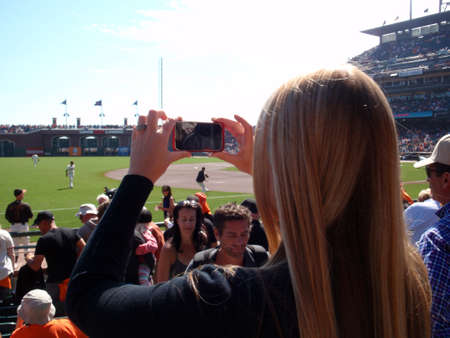 baseball crowd: SAN FRANCISCO - OCTOBER 2: Lady uses Iphone cellphone camera in a plastic case to Photograph baseball game from the crowd between innings as the players warm-up. October 2 2010 at the ATT Park San Francisco California.