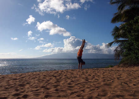 Man in a blue shirt and orange shorts Handstands on an empty Beach on Maui, Hawaii. photo