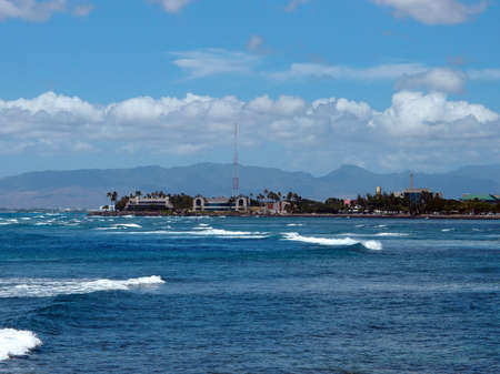 Waves roll along the coast of Kakaako Waterfront Park and surrounding buildings on Oahu, Hawaii.