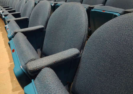 Curved Rows of Light Blue Cloth Seat with armrests in a theater. photo