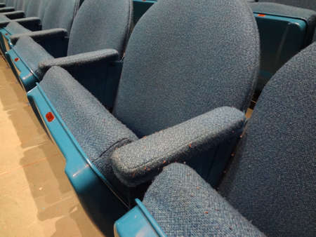 Curved Rows of Light Blue Cloth Seat with armrests in a theater.  With Number 31 visible on seat. photo