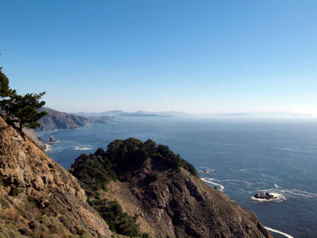 California scenic coastal cliffs with the city of San Francisco in the the far distant background. Blue sky and waves breaking against the shore.