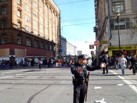 motor officer: SAN FRANCISCO, CA - NOVEMBER 3: SFPD Police officers holds out hands to wave on crowd on a closed market street and Seventh street to help keeping the order with a bus and buildings in the area after Giants World Series Parade Nov. 3, 2010 San Francisco,