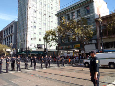 SAN FRANCISCO, CA - NOVEMBER 3: Police officers stand in line across market street at the six street intersection during the Giants World Series Parade as a Police van rolls by on Nov. 3, 2010 San Francisco, CA.