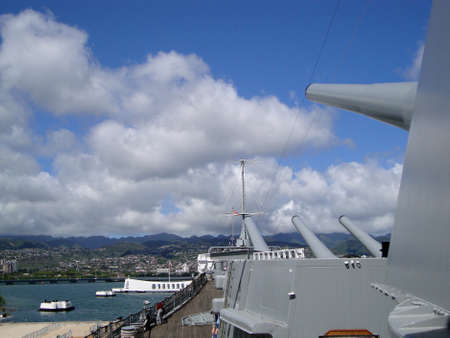 Large Metal Guns and deck on the Historic Battleship the USS Missouri looking out into Pearl Harbor with the Arizona Memorial visible on Oahu, Hawaii.  Nice day with blue sky and beautiful clouds.