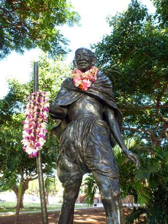 leis: Statua di Mahatma Ghandi in possesso di un bastone da passeggio e indossando leis reali che hanno vissuto 2 Ottobre 1869 - 30 Gennaio 1948, si trova nel Kapiolani Park a Waikiki, Hawaii.