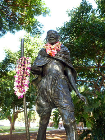 leis: Statue of Mahatma Ghandi holding a walking stick and wearing real leis Who lived October 2, 1869 - January 30, 1948, located in Kapiolani Park in Waikiki, Hawaii.