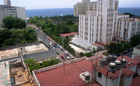 Tall Hotel buildings, Rooftops, and the street below with cars and trees stretching to the water in Havana, Cuba. 2004.