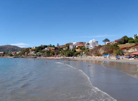 Beautiful tropical sandy beach with people playing in the water, buildings and hills in the background in Zihautanejo, Mexico.