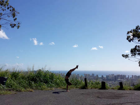 Man wearing t-shirt, shorts and rubber slippers Handstanding with a curved back at Tantalus lookout point with the city of Honolulu, Hawaii and ocean visible in the distance.