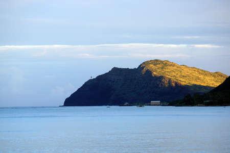 windward: Waimanalo bay, Pier, and Makapuu Point with Makapuu Lighthouse visible on cliffside mountain at dusk on windward coast of Oahu, Hawaii.