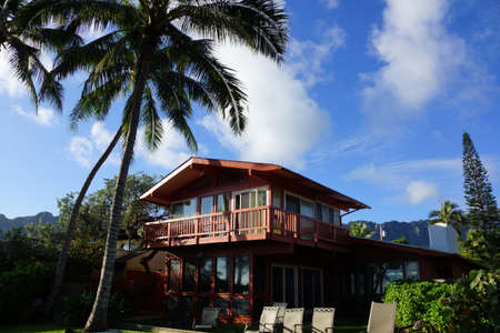Red Two Story Beach House with tall coconut trees, lawn chairs, and mountains  on Oahu, Hawaii on a beautiful day.