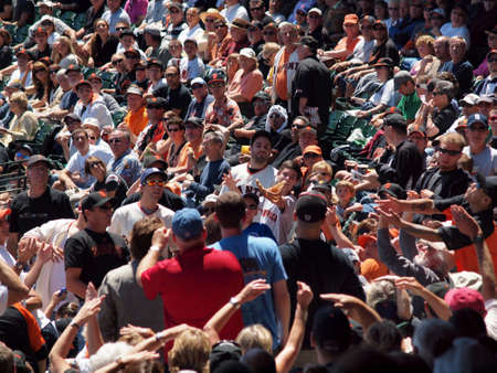 SAN FRANCISCO - AUGUST 12:  Excited fans reach with hands and gloves for foul ball hit in the stands at Giants Baseball game August 12 2010 at the ATT Park San Francisco California. Editorial