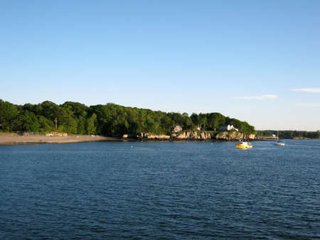 Beach, house on island shore and boats in the waters of Portland Harbor in Maine. photo