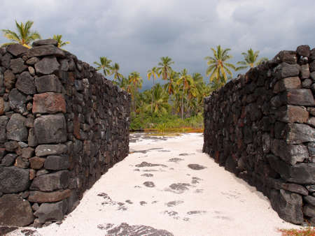 refuge: Massive man-made Rock Walls of Puuhonua o Honaunau - Place of Refuge, A wall up to 10 feet high and 17 feet thick surrounded the royal compound.  Hawaiian historic site on the water with coconut trees and lava rock walls surrounding a sandy path in a Nat Stock Photo