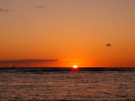 Sunset over the horizon of Pacific Ocean in Waikiki with boats in the water of Oahu, Hawaii. photo