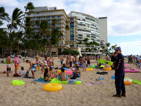 HONOLULU, HI - JANUARY 21: Honolulu Police officer calls for backup as he inspects beach party of young people with water floatation devices on kaimana beach January 21, 2013 in Honolulu, Hawaii.