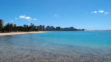 People play at Ala Moana Beach with buildings of Waikiki and iconic Diamondhead in the distance during a beautiful day on the island of Oahu, Hawaii.  photo