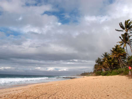 banzai pipeline: Waves lap on Beach at the world famous Banzai Pipeline on a cloudy day on Oahu, Hawaii.