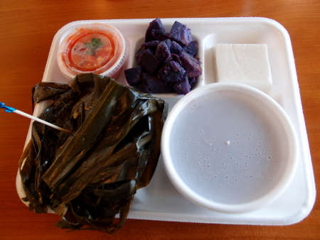 Hawaiian Lau Lau plate Served with FreshDay Old Poi in bowl, Uala (sweet Potato), Haupia with Lomi Salmon in a plastic container on a Styrofoam plate on a table. photo