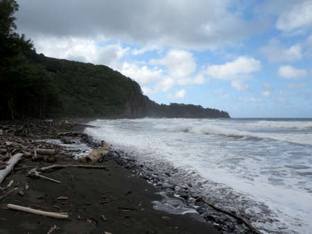 Pololu Valley black sand beach in Big island, Hawaii surrounded by Valley cliffs and the dramatic northeastern coastline. photo