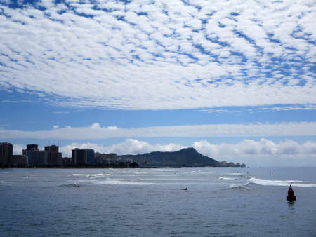 Waves roll in in front Waikiki and iconic Diamondhead in the distance during a beautiful day with amazing clouds on the island of Oahu, Hawaii. photo