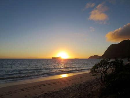 Early Morning Sunrise on Waimanalo Beach over Rabbit Island bursting over the island on Oahu, Hawaii.  With Lighthouse on mountain in distance.
