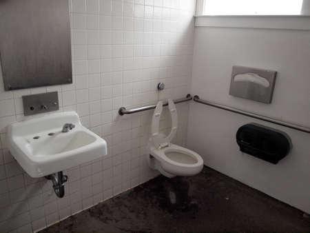 Inside Public Bathroom with sink, toilet, soap dispenser, and handicap railings on Angel Island, California.